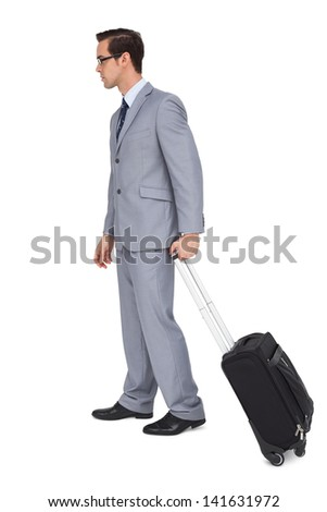 Young businessman with glasses holding a trolley on white background - stock photo