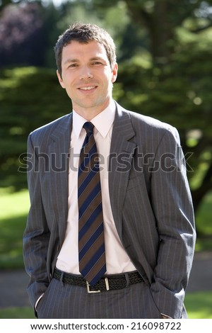 Young businessman with hands in pockets outdoors, smiling, portrait - stock photo