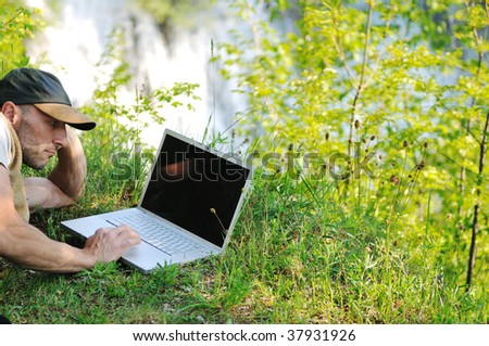 young businessman with hat work on thin laptop outdoor in nature with beautiful waterfalls in background representing freedom and wireless technology concept