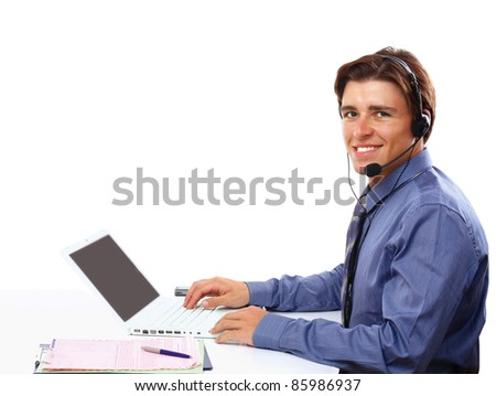 Young businessman with  headset in front of laptop smiling at camera isolated on white - stock photo