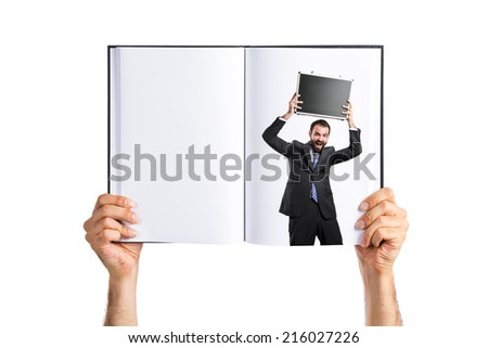 Young businessman with his briefcase printed on book - stock photo