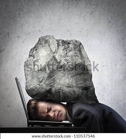 Young businessman with his head squeezed between a laptop keyboard and a rock - stock photo