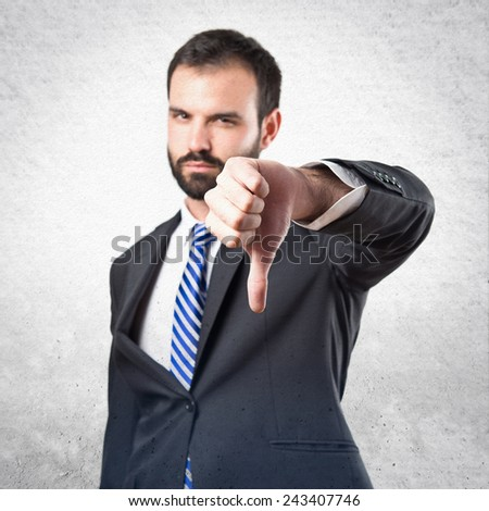 Young businessman with his thumb down over textured background