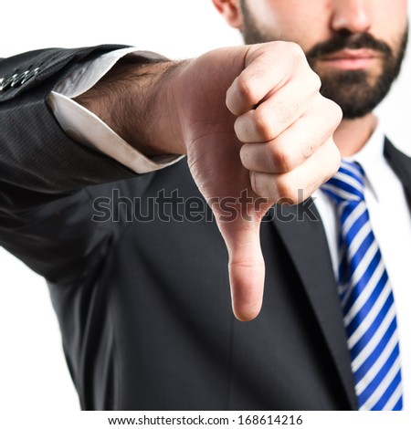 Young businessman with his thumb down over white background  - stock photo