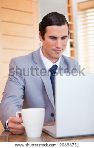 Young businessman with laptop and coffee - stock photo