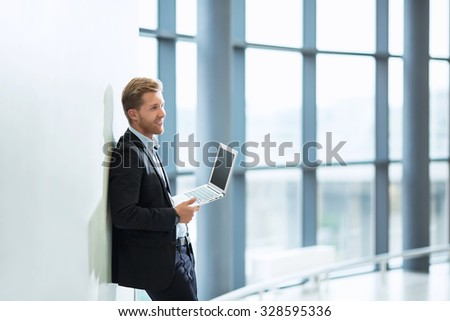 Young businessman with laptop indoors - stock photo