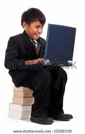 young businessman with laptop sitting on a stack of books