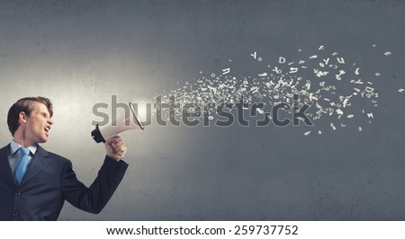 Young businessman with megaphone announcing some information - stock photo