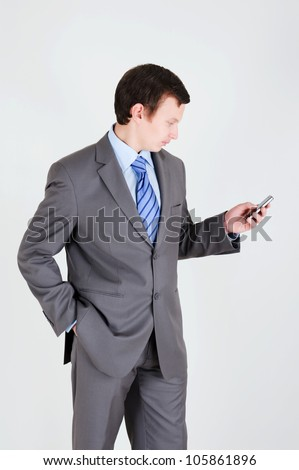 Young businessman with mobile phone and his hand in the pocket - stock photo