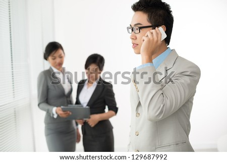Young businessman with phone on the foreground