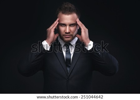 Young businessman with problems and stress on dark background - stock photo