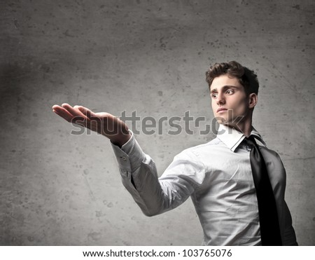 Young businessman with raised hand - stock photo