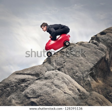 young businessman with red car descends from rocks - stock photo