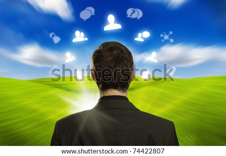 Young businessman with social network icons floating around his head 3 - stock photo