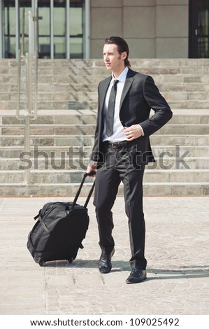 Young businessman with suitcase. - stock photo