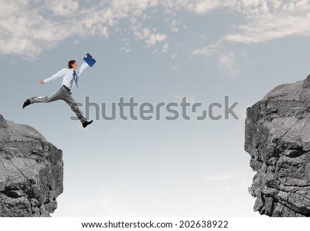 Young businessman with suitcase jumping over mountain gap - stock photo