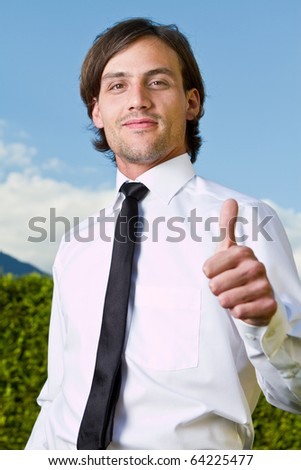 Young businessman with thumb up sign over a blue sky in the background.
