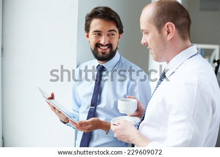 Young businessman with touchpad showing data to his colleague at meeting - stock photo