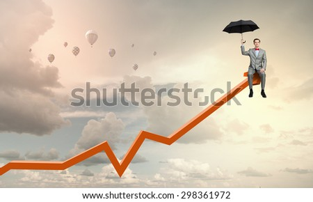 Young businessman with umbrella sitting on increasing arrow