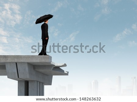 Young businessman with umbrella standing on bridge