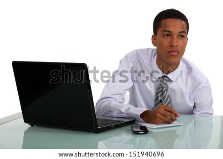 young businessman working at his desk and thinking - stock photo