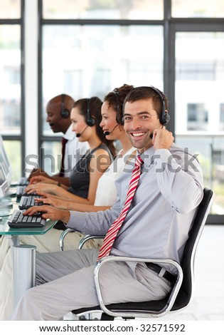Young businessman working in a call center smiling at the camera