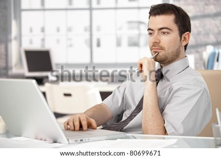 Young businessman working in bright office, sitting at desk, using laptop.?