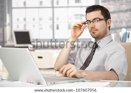 Young businessman working in bright office, sitting at desk, using laptop, wearing glasses.