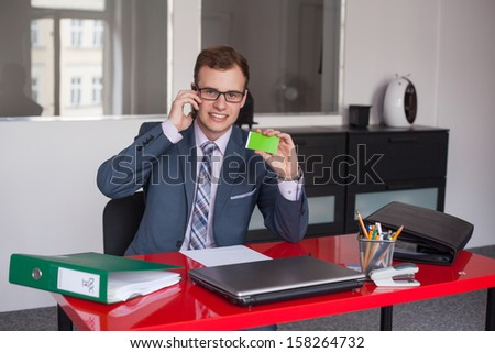 Young businessman working in bright office, sitting at desk with business card and mobile phone. - stock photo