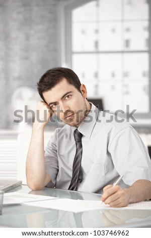 Young businessman working in bright office, sitting at desk, writing notes, thinking. - stock photo