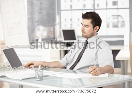 Young businessman working in bright office, using laptop, writing notes.?