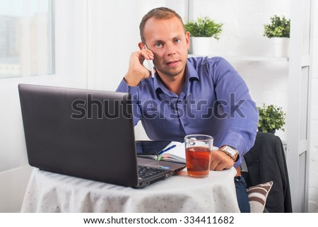 Young businessman working in office, sitting at a table, looking straight and talking on the phone.