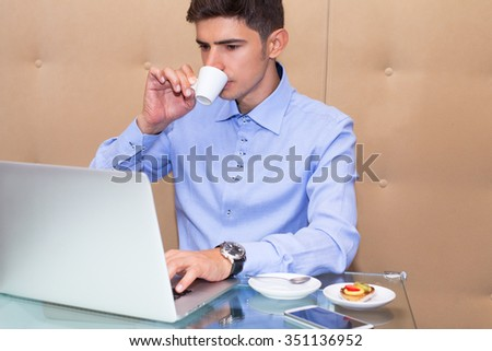 Young businessman working on computer. Successful man sitting at the table in his office uses a Mac with internet connection