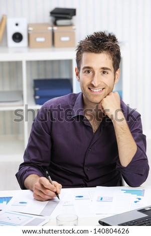 Young businessman working on desk, looking at camera, smiling