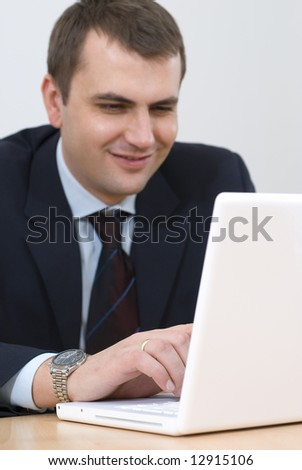 Young businessman working on lap-top and smiling isolated on white stock photo