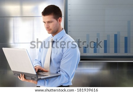 Young businessman working on laptop computer, standing by big LCD display with business diagram. - stock photo