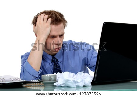young businessman working on laptop looking exasperated