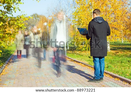 Young businessman working on laptop through wireless technology in the park. Motion blurred people walking along a path