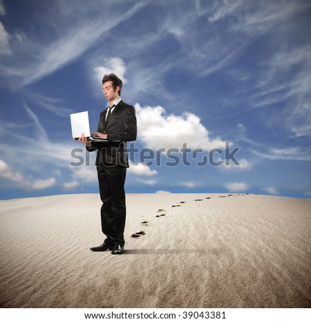 young businessman working with laptop in a desert
