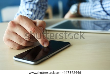 Young businessman working with modern devices, digital tablet computer and mobile phone. Analyze plans, papers, hands keyboard. Blurred background, film effect - stock photo