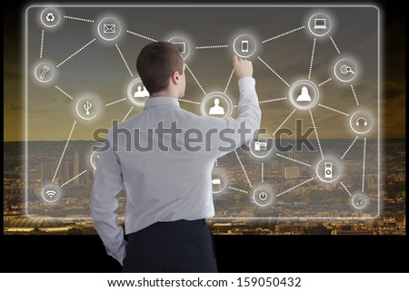 Young businessman works on a big touchscreen with a city skyline as background