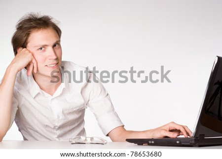 young businessman works with laptop at table