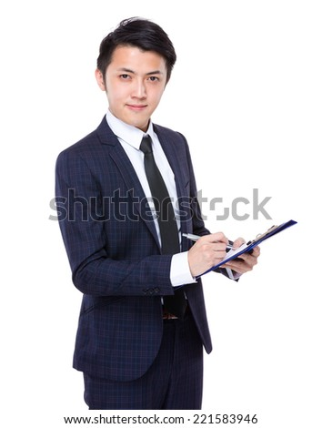 Young businessman write on clipboard - stock photo