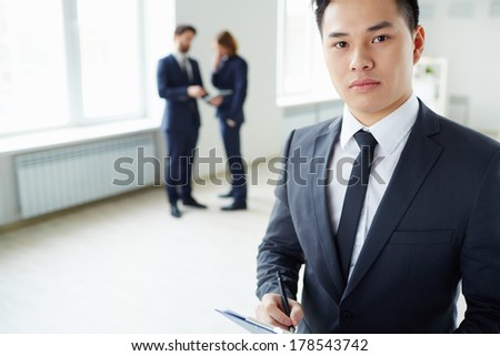 Young businessman writing plan and looking at camera in working environment - stock photo