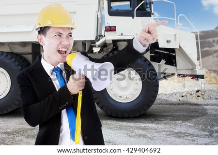Young businessman, yelling uses a megaphone in the mining site with a big truck on the background