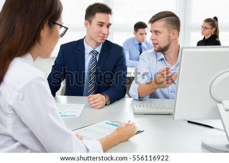 Young businessmen discussing a project with laptop at modern office