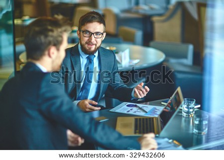 Young businessmen discussing ideas and strategies in office - stock photo