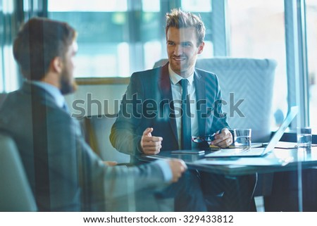 Young businessmen discussing working plans in office - stock photo
