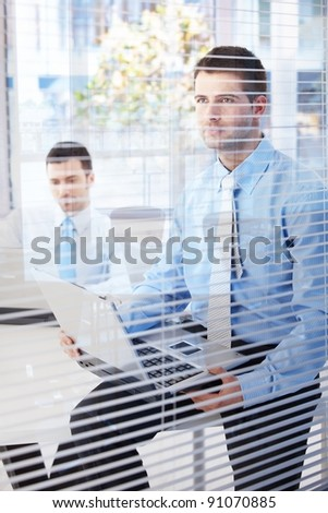 Young businessmen working in bright office behind blind.? - stock photo