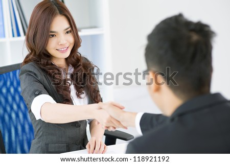 Young businesspeople concluding a deal and sealing it with a handshake - stock photo